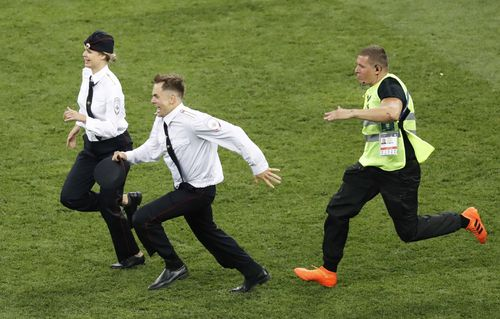 A security guard (R) chases a man and woman who invaded the pitch during the second half of the World Cup final between France and Croatia at Luzhniki Stadium in Moscow on July 15, 2018. Russian protest group and musical act Pussy Riot has claimed responsibility for the incident. (Kyodo via AP Images)