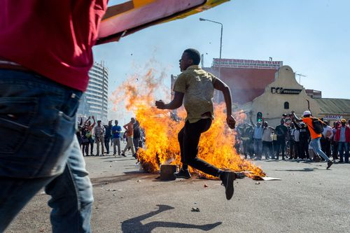 People gather around a fire on the street during a protest against polling results in Harare, Zimbabwe, 01 August 2018 (issued 02 August 2018). The day saw protests turn violent when police fired rubber bullets and teargas, before the army was called in and began firing live rounds. EPA/YESHIEL PANCHIA