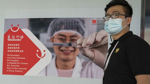 An employee of SinoVac stands near an advertisement for its SARS CoV-2 Vaccine for COVID-19 named CoronaVac at its factory in Beijing on Thursday, Sept. 24, 2020