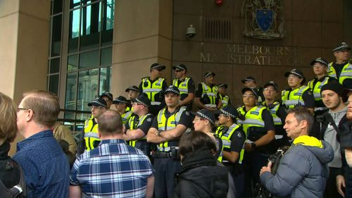 Officers line the steps of the Melbourne Magistrates' Court ahead of Cardinal Pell's arrival.