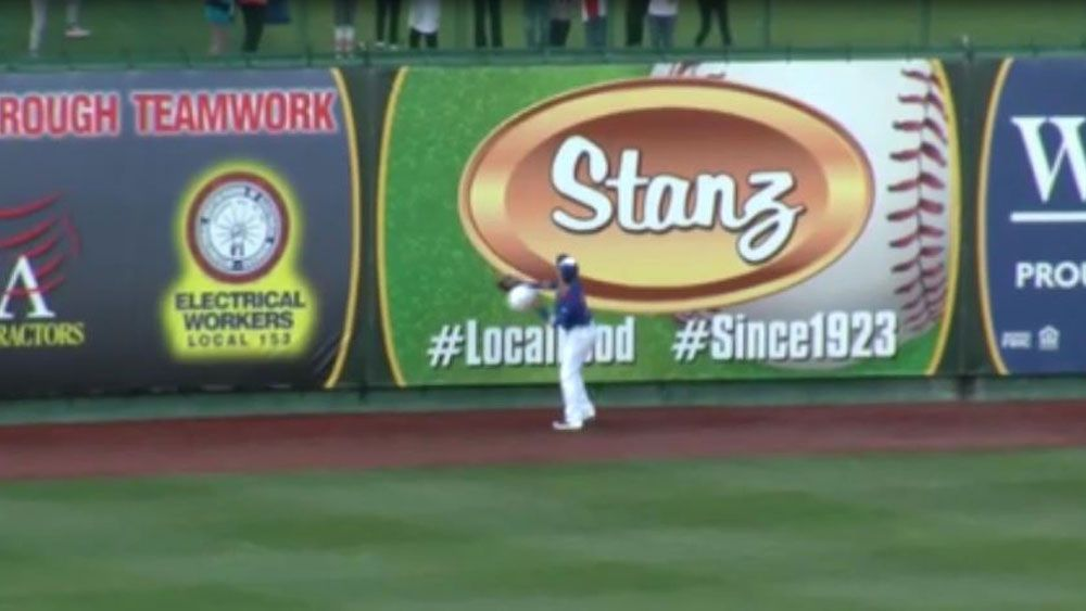 South Bend Cubs outfielder DJ Wilson throws beach ball into wind in Minor League Baseball
