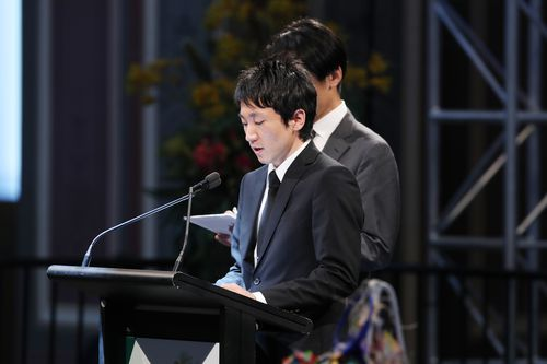 Junpei Kanno talks about the loss of his brother Yosuke at a public memorial service in the Melbourne Royal Exhibition building in 2018.