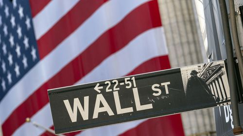 Monday, Sept. 21, 2020, file photo, a Wall Street street sign is framed by a giant American flag hanging on the New York Stock Exchange in New York