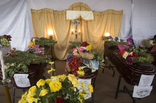 Coffins covered with flowers as the funerals for the victims get under way. Picture: AP