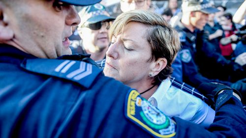 Police rush to the assistance of Christine Forster as she's caught up in protests at an event for her brother, former prime minister Tony Abbott, in Redfern, Sydney. (AAP)