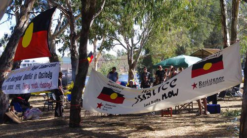 """Aboriginal flags and protest banners at an Aboriginal """"tent embassy"""" appear at Heirisson Island in Perth in 2012. (AAP)"""