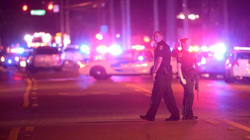 Police officers stand guard down the street. (AP)