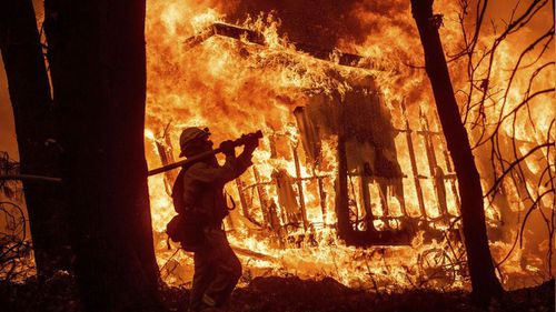 A firefighter battles the fierce blaze as it consumes a home in California.