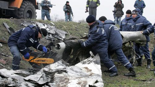 The crews cut pieces of the debris with metal saws at the crash site near the village of Grabove, Ukraine. (AAP)