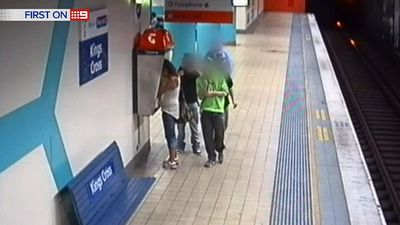 The group stops at a phone booth to riffle through the stolen handbag. (9NEWS)