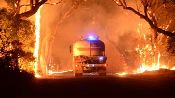 A truck weaves its way through the fire at Tarrara Lane in Bradbury.