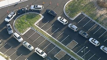 Cars snake around the car park as people wait to be tested in Keysborough in Victoria.