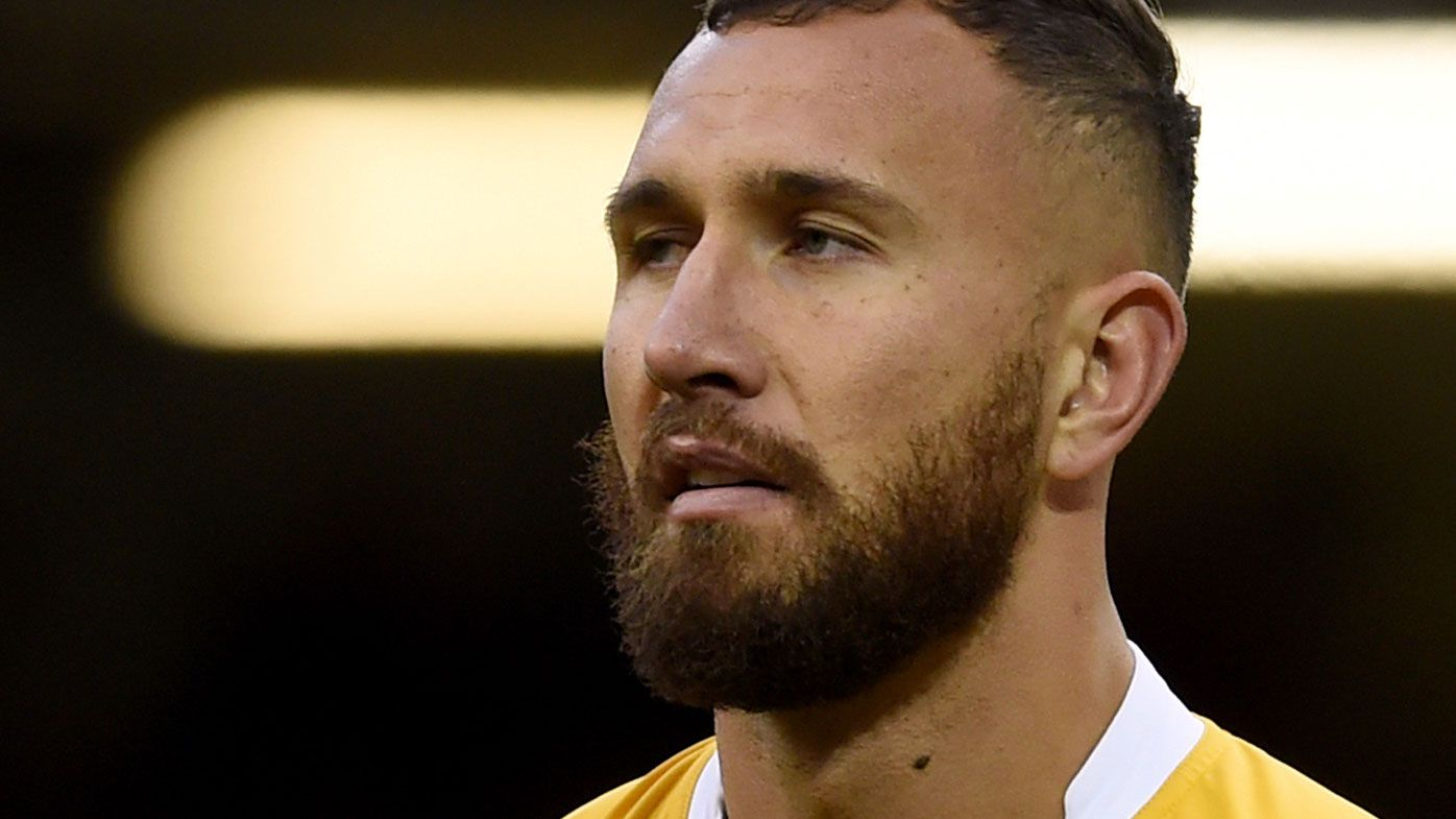Quade Cooper is content to warm the bench for the Wallabies. (AAP)
