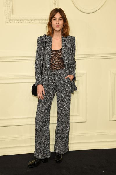 With her gamine model looks, shaggy natural waves and a risqué lace top, Alexa Chung softens a classic tweed Chanel number.