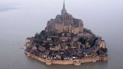 """Thirty thousand people flocked to Mont Saint-Michel to see the """"tide of the century"""" surround the picturesque French landmark.<br><br>  A record-breaking crowd gathered at the rocky island topped with a Gothic Benedictine abbey to watch the sea surge up the bay on the Normandy coast.<br><br>  The water covered a causeway that usually links the mountain to the coastline."""