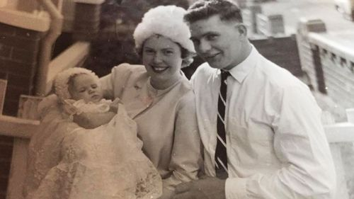 Kim, pictured with her mother Jean and father Alan, on her christening day.