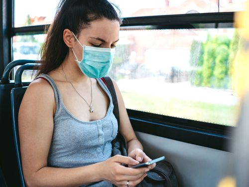 Young woman wearing face mask on public transport.