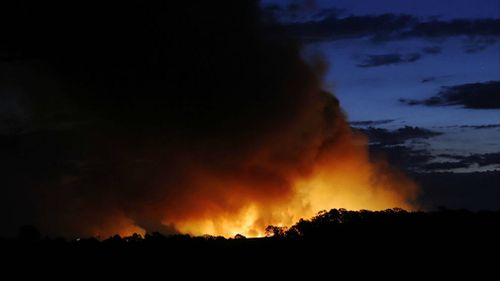The glow of a bushfire at dusk as it burns through Richmond Vale near Cessnock in the Hunter Valley. (AAP)