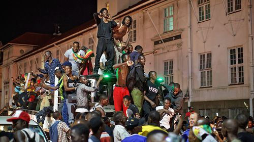 Celebrations marking the end of Robert Mugabe's 37-year rule lasted long into the night in Harare. (Photo: AP).