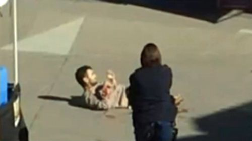 The armed man lying on the ground after being shot.