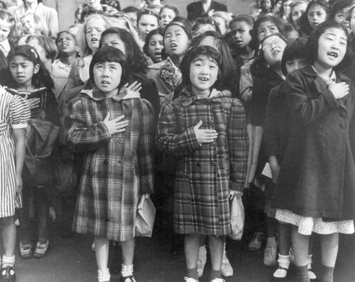 In this April 1942 photo, children at the Weill public school in San Francisco recite the Pledge of Allegiance. Some of them are evacuees of Japanese ancestry who were housed in War Relocation Authority centers for the duration of World War II. (AP)