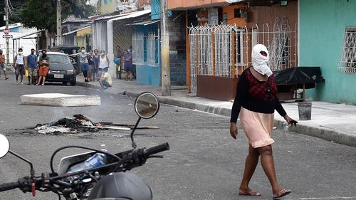 A woman walks past wearing a cloth around her head to ease the smell of death coming from the body of a person, who allegedly died from the new coronavirus, placed on the porch of a home wrapped in a black tarp, in a suburb of Guayaquil, Ecuador,