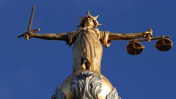 A statue representing Justice stands atop a court building.