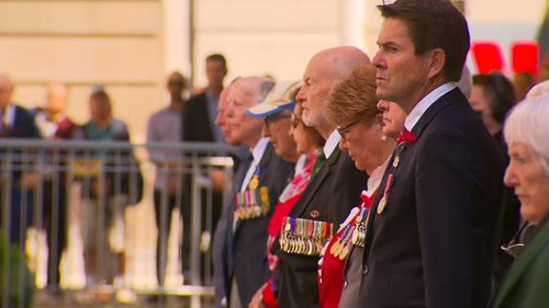 Audience of the 2020 Remembrance Day service in Canberra standing during the sounding of The Last Post.