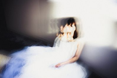 Sad blurry bride sitting at window.