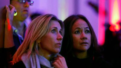 Britons watch a livestream of the election from a screen at the US embassy in London. (AAP)