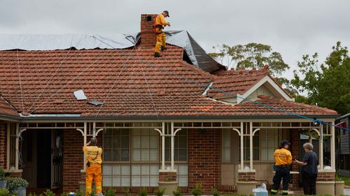 NSW Rural Fire Service workers are seen repairing a house that was damaged in a hail storm overnight in Berowra Heights.