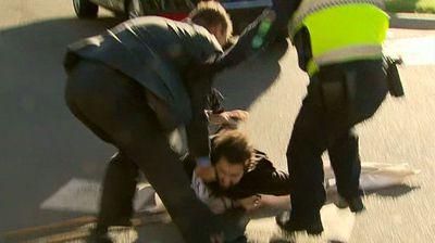 A protester gets body-slammed by police after lunging at Julie Bishop. (Nine News)