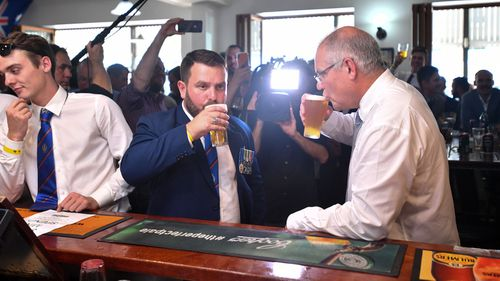 Liberal candidate for Herbert Phillip Thompson and Prime Minister Scott Morrison have a beer at The Australian Hotel in Townsville on Anzac Day.