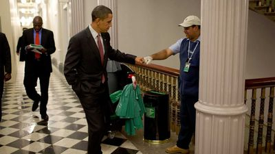 Obama shares a fist-bump with a janitor.