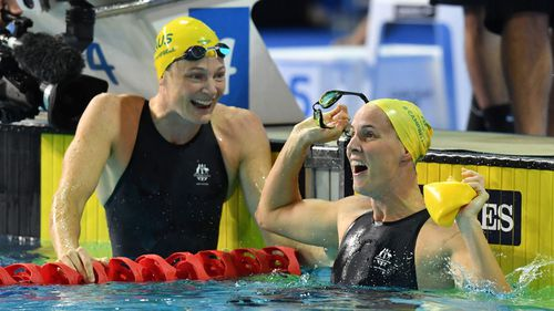 Bronte Campbell celebrates, as her sister Cate Campbell looks on, after winning the women's 100m freestyle final on day five.