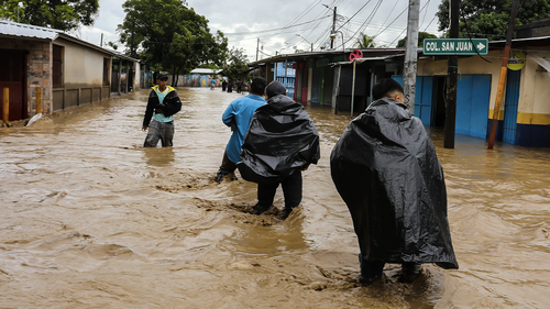 People wade trough a flooded street in Honduras on November 18, 2020, following the passage of Hurricane Iota.