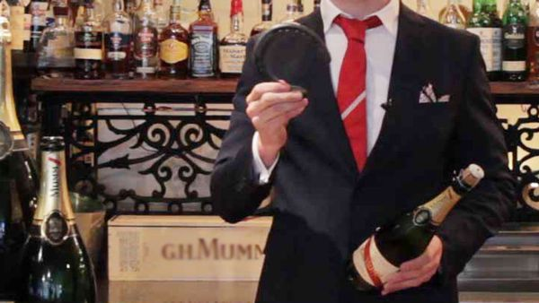 Champagne ambassador Chris Sheehy opens bottle with a horseshoe for Melbourne Cup