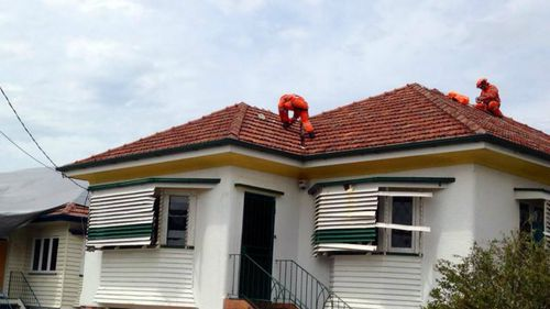 SES workers finish roof repairs on a house in Brisbane. (9NEWS)