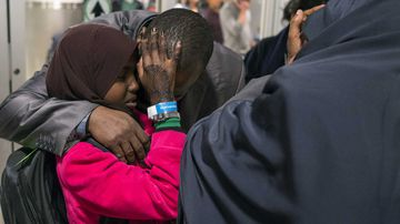 Miski Shalle, 11, embraces her father Ismail Issack as she and her sister, part of Somalian family who have been separated from their parents who have been living in the United States, reunite for the first time in seven years. (AAP)