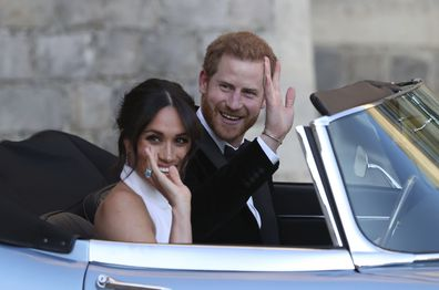 FILE - In this Saturday, May 19, 2018 file photo the newly married Duke and Duchess of Sussex, Meghan Markle and Prince Harry, leave Windsor Castle in a convertible car after their wedding in Windsor, England, to attend an evening reception at Frogmore House, hosted by the Prince of Wales. Prince Harry and Meghan Markle are to no longer use their HRH titles and will repay £2.4 million of taxpayer's money spent on renovating their Berkshire home, Buckingham Palace announced Saturday, Jan. 18. 202
