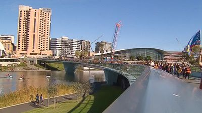 Thousands of fans make their way over the footbridge on their way into Adelaide Oval. (9NEWS)
