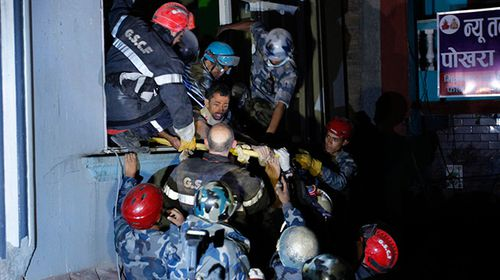 Rishi Khanal is rescued after four days trapped inside a collapsed apartment complex. (AAP)
