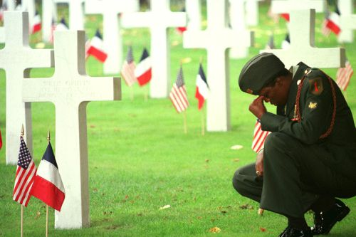 An unidentified soldier of the U.S 1st. Infantry division, based in Germany, pays respects at a grave of the U.S World War I cemetery.