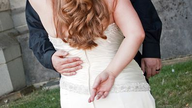 A bride stands with her back toward the camera, with her fingers crossed.