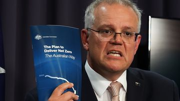 Prime Minister Scott Morrison hold the plan he claims will lead Australia to net zero by 2050.