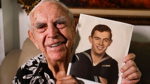 US Navy veteran Daryl Weathers with a photo from his World War II service. He was aboard the USS Abner Read after it hit a sea mine left by the Japanese off Alaska.