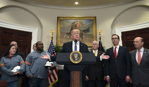 President Donald Trump, center, speaks in the Roosevelt Room of the White House in Washington today. (AAP)