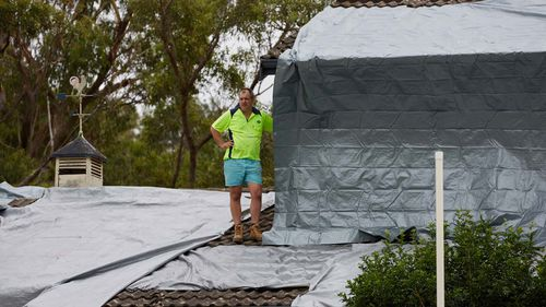 A resident is seen on the roof of a house that was damaged in a hail storm overnight in Berowra Heights.