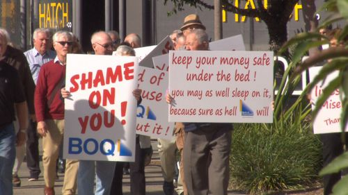 The victims took their protest to the doors of the bank.