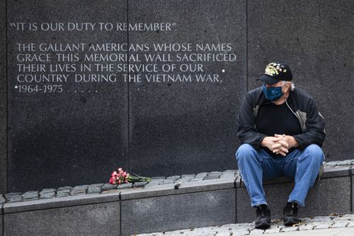 Vietnam Veteran Kitch Kichula, wearing a protective face mask as a precaution against the coronavirus, pays his respects at the at the Vietnam War Memorial, in Philadelphia, on Memorial Day